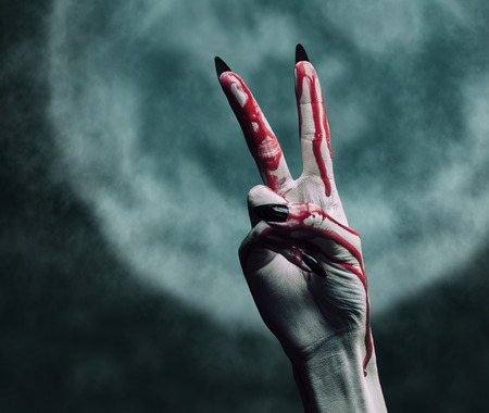 undead: Vampire hand in blood on  full moon, peace hand sign. Halloween or horror theme Stock Photo