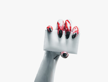 Vampire hand holds empty card on white , space for text. Halloweenhorror theme