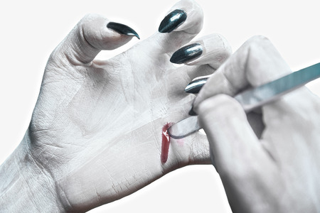 Unrecognizable dead woman writing on her hand by scalpel. Space for text on hand, Halloweenhorror theme photo