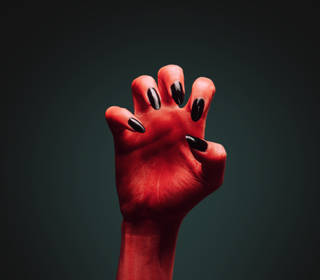 scary hand: Scary red devil hand on dark . Halloween or horror theme