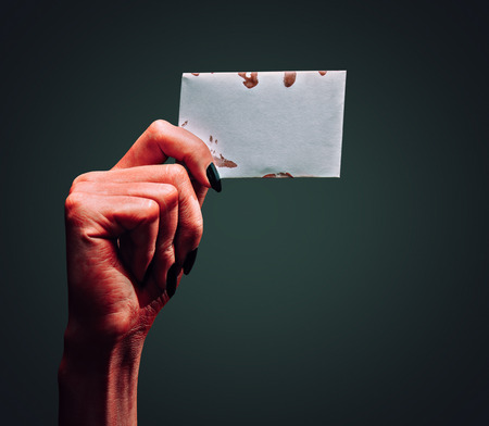 zombie hand: Red demon or devil hand holding empty card on dark , space for text. Halloweenhorror theme Stock Photo