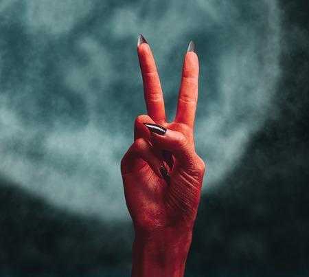 red sign: Red devil hand on dark , peace hand sign. Halloween or horror theme