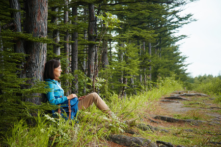 ecotourism: Hiker young woman with backpack rests near tree in summer forest