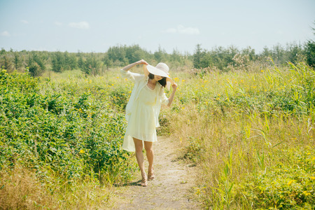 brim: Beautiful fashionable woman walking in the summer park. Woman in yellow dress and hat with wide brim