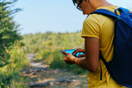 person outdoors: Traveler young man looking for something on tablet PC in summer forest
