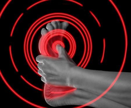 La mujer sostiene su pie, el dolor en el pie, imagen monocroma, área de dolor del color rojo