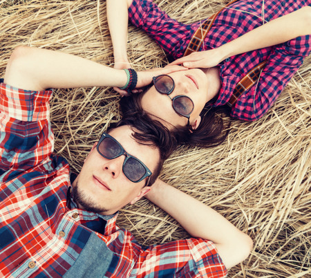 Beautiful couple in love is lying on dry grass, man is stroking the face of girl photo