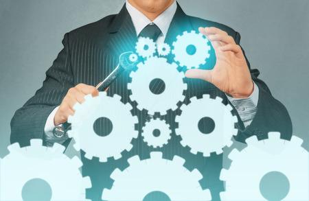 Affaires non reconnaissable détient une clé en métal avec roues dentées, concept de création d'entreprise