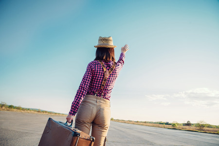 Traveler hipster woman with vintage suitcase waves her hand away, rear view, theme of travel, space for text photo