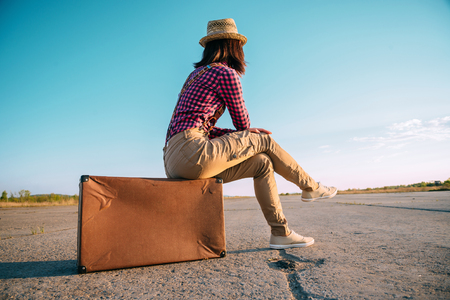 Traveler woman sits on retro suitcase and looks away on road, theme of travel, space for text