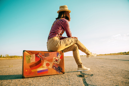 Traveler žena sedí na retro kufr a vypadá pryč na silnici. Kufr se známkami vlajkami zastupují každou zemi cestoval.