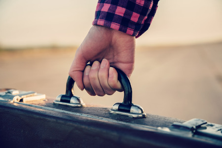 holding close: Close-up image of female hand with retro suitcase, face is not visible