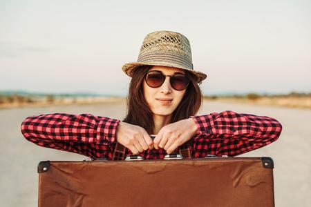 Smiling woman tourist holds vintage suitcase, travel theme photo
