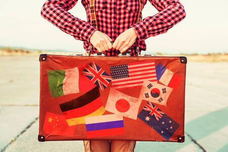 reiste: Frau h�lt braunen Vintage-Koffer, Gesicht ist nicht sichtbar. Suitcase mit Briefmarken Fahnen, die jedes Land gereist. Lizenzfreie Bilder