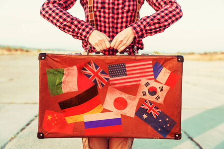 traveled: Woman holds brown vintage suitcase, face is not visible. Suitcase with stamps flags representing each country traveled.