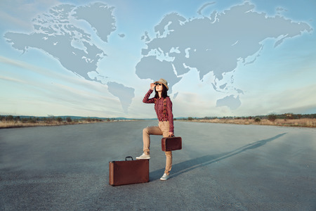 Traveler  woman with suitcase looks on road. World map in the sky photo