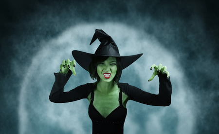 mage: Spooky green witch performs magic on full moon . Halloween, horror theme