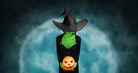 scary witch: Green witch holds Halloween carved pumpkin on  full moon. Halloween, horror theme