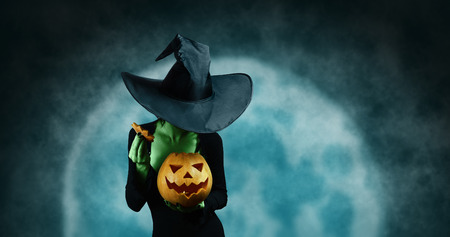 Green witch opening Halloween carved pumpkin on full moon . Halloween, horror theme
