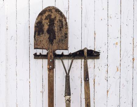 mattock: Gardening tools hoe, shovel and rake near a wooden wall