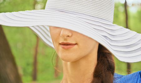 brim: Mysterious woman in hat with wide brim in park in the summer