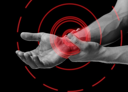 Acute pain in a male wrist. Man holds his hand, black and white image, pain area of red color photo