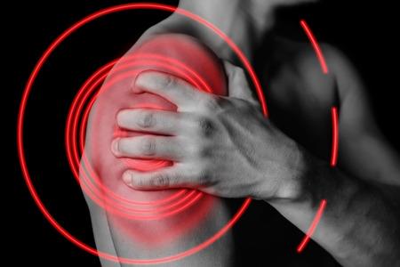 Unrecognizable man compresses his shoulder, pain in the shoulder, side view, pain area of red color Standard-Bild