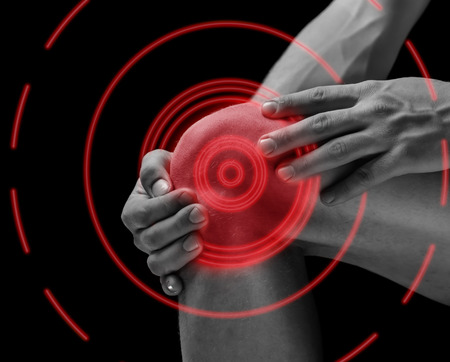 Pain in the male knee joint, pain area of red color Standard-Bild