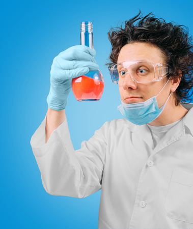 Crazy laboratory technician is looking at test tube with red liquid