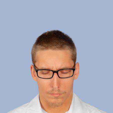 ojos cerrados: Retrato de un hombre con los ojos cerrados sobre un fondo azul