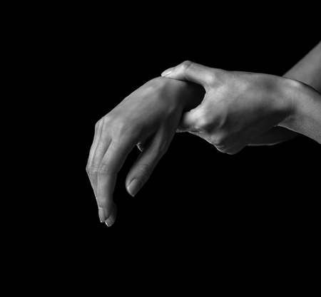 Pain in a female wrist. Woman holds her hand, monochrome image photo
