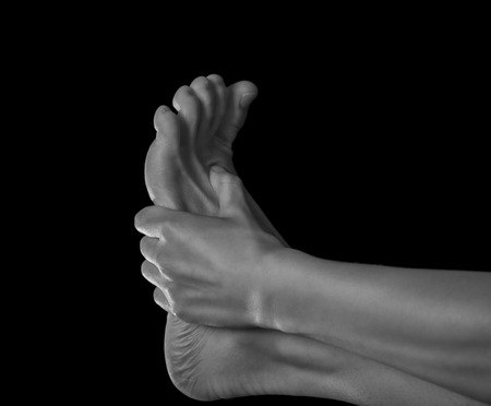 Woman holds her foot, pain in the foot, monochrome image Stockfoto