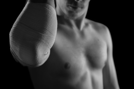 Bandaged male elbow joint, sprain, monochrome image photo