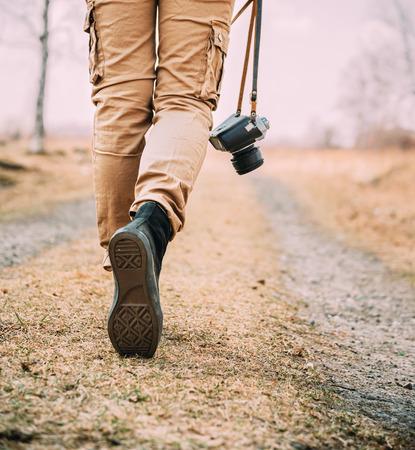 Frau mit alten Fotokamera Traveler Spaziergänge auf einer Straße, Gesicht nicht sichtbar ist