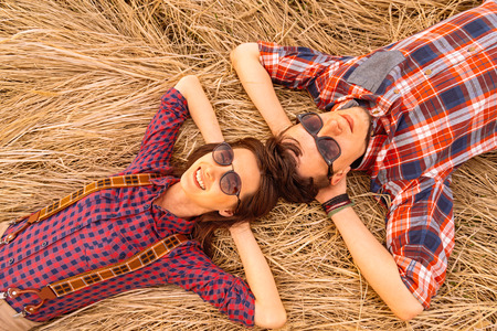 Young hipster couple in love rests on dry grass Zdjęcie Seryjne