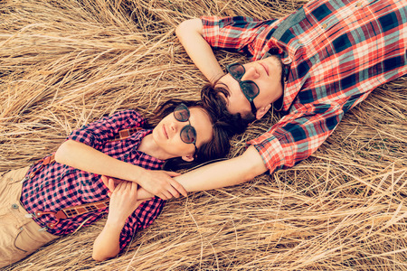 Hipster style couple in love is lying on meadow