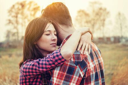 ojos cerrados: Mujer joven con los ojos cerrados abraza a un hombre, escena tranquila