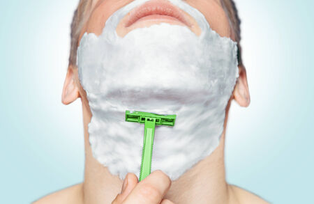 Man with foam on his face is shaving with green razor photo