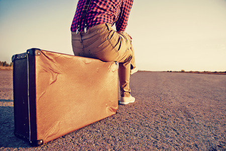 Unrecognizable female traveler sits on suitcase on road, space for text
