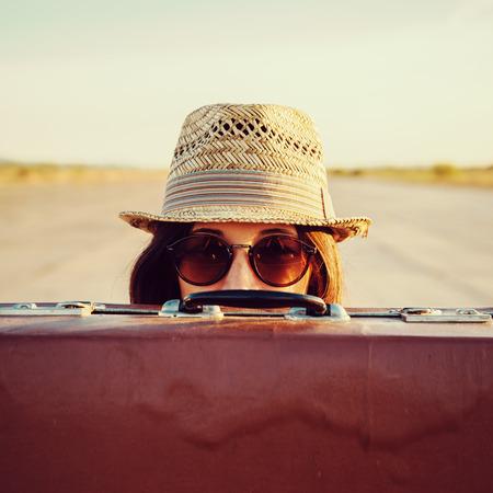 Hipster kobieta w kapeluszu i okularach wygląda z rocznika walizki