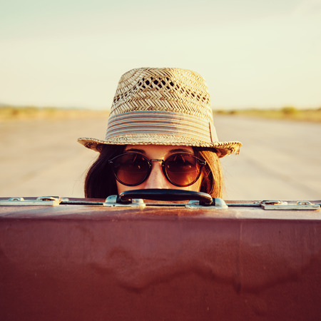 females only: Hipster woman in hat and glasses looks out from vintage suitcase