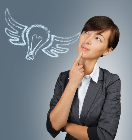 Young pensive woman looks at light bulb with wings, concept of new idea and inspiration photo