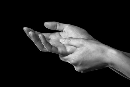 arm pain: Woman holds her hand, pain in the wrist, black and white image