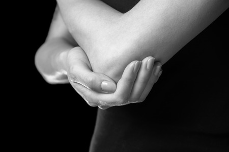 Unrecognizable woman holds her elbow joint, acute pain in the elbow, monochrome image photo