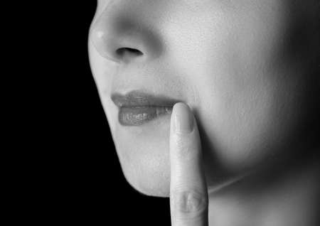 herpes: Unrecognizable woman is touching corner of lips, herpes on lip, monochrome image Stock Photo