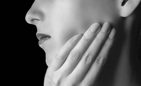 unrecognizable: Woman is touching her cheek, toothache, black and white image