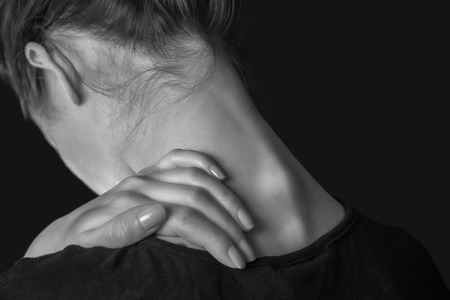 woman from behind: Unrecognizable woman touches her neck, pain in the neck, rear view Stock Photo