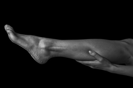 calf pain: Woman holds her leg, pain in the female calf muscle, monochrome image