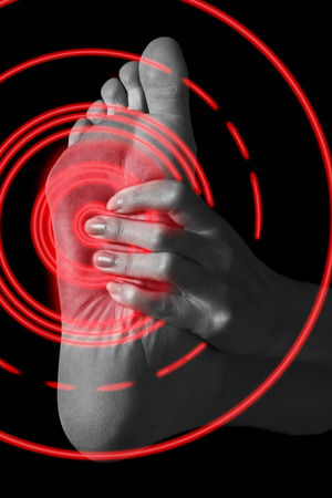 El dolor en el pie de la mujer, imagen monocroma, área de dolor del color rojo Foto de archivo