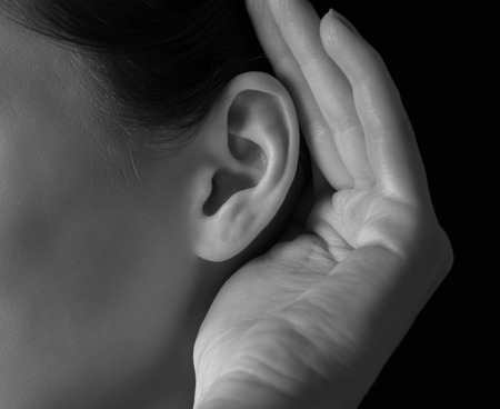 1: Unrecognizable woman holds her hand near ear and listens, close-up Stock Photo
